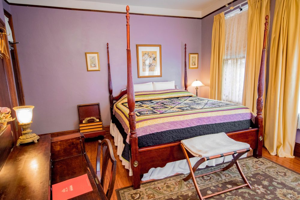 Hotel room with purple walls and large bed daytime angle 2