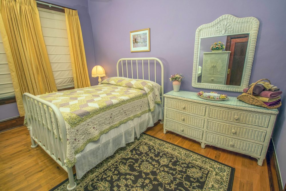 Hotel rooms with purple walls and yellow curtains