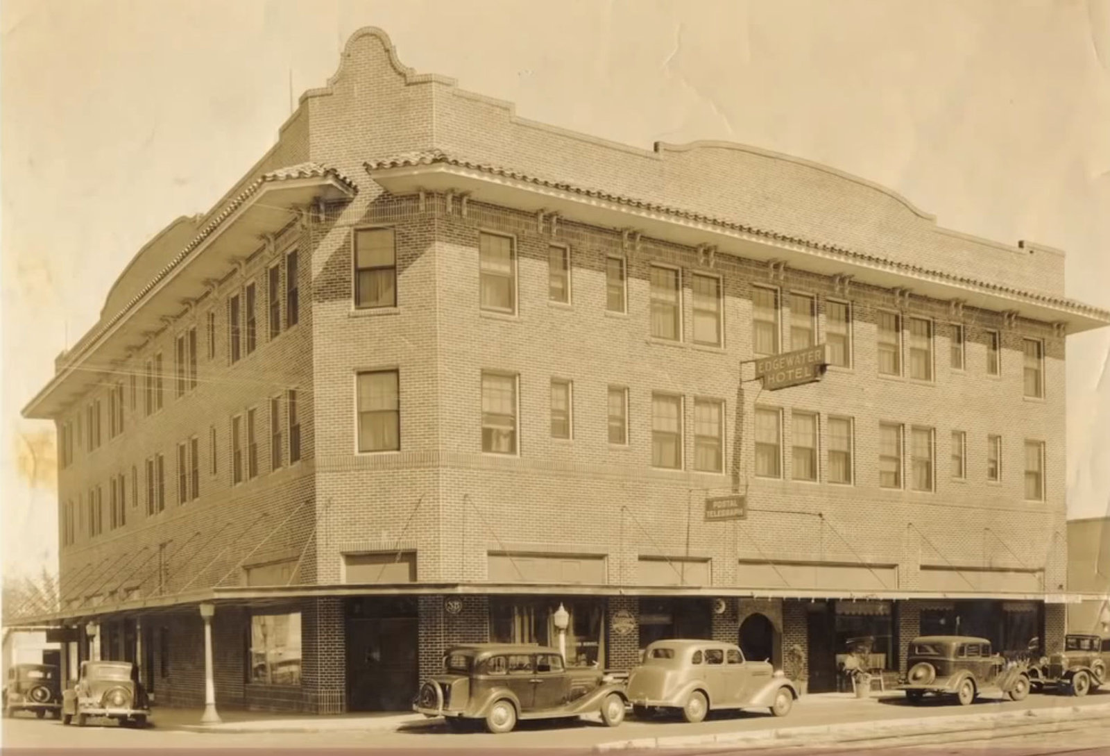 Aged picture of Hotel Edgewater with old cars parked outside